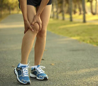 Runner holding their knee in pain